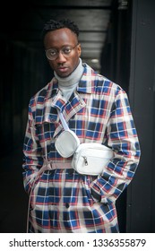 LONDON - FEBRUARY 17, 2019: Stylish attendees gathering outside 180 The Strand for London Fashion Week. A man in a white and red plaid coat