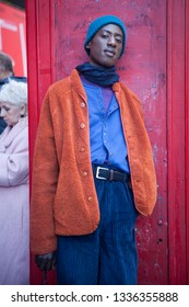 LONDON - FEBRUARY 17, 2019: Stylish attendees gathering outside 180 The Strand for London Fashion Week. The man in blue velvet pants, orange fur jacket and knitted hat