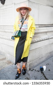 LONDON - FEBRUARY 17, 2019: Stylish attendees gathering outside 180 The Strand for London Fashion Week. Woman in pink hat is wearing a yellow raincoat, a white T-shirt and a black midi skirt