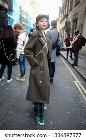 LONDON - FEBRUARY 17, 2019: Stylish attendees gathering outside 180 The Strand for London Fashion Week. The girl wears a beige trench coat and checkered wide trousers and a cap.