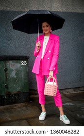 LONDON - FEBRUARY 17, 2019: Stylish attendees gathering outside 180 The Strand for London Fashion Week. Girl in a pink classic suit with an umbrella