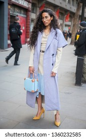 LONDON - FEBRUARY 17, 2019: Stylish attendees gather outside 180 Strand for London Fashion Week. Artist Ciinderella B wearing lavender long sleeveless coat, Gray sweater, blue culottes, baby blue bag