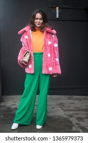 LONDON - FEBRUARY 17, 2019: Stylish attendees gathering outside 180 The Strand for London Fashion Week. Girl in a pink faux-fur coat in white speckles and green flared jeans