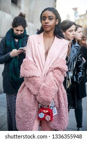 LONDON - FEBRUARY 17, 2019: The woman is dressed in a pink fur coat made of faux fur, pantsuit: jacket and pants-cigarette with a red handbag baby with applique at London Fashion Week.