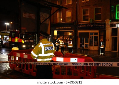 London, February 2017 - An officer from the Metropolitan Police in London stands guard as fire fighters deal with an incident the background. His HiVis jacket reflects the light.