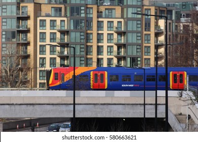 London, February 2017. A passenger train operated by South West trains travels between Wandsworth Town and Clapham Junction railway stations against a backdrop of residential  properties.