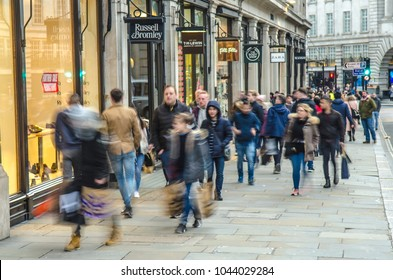 London- February, 2018: Regent Street shoppers. Many people motion blurred and carrying shopping bags past fashion shops
