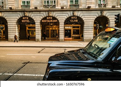 LONDON- FEBRUARY, 2020: The Ritz London, a landmark 5 star luxury hotel in the heart of Mayfair with a London black taxi cab in front.