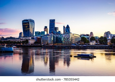 London financial district during sunrise with its reflection from river Thames