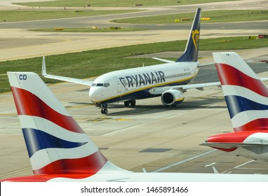 LONDON GATWICK AIRPORT - APRIL 2019: Boeing 737 jet operated by budget airline Ryanair taxiing after landing at London Gatwick airport. The view is framed by tail fins of rival airline British Airways