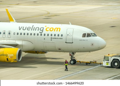 LONDON GATWICK AIRPORT - APRIL 2019: Airbus A320 jet operated by Spanish airline Vueling being pushed back by a tug on departure from London Gatwick Airport.