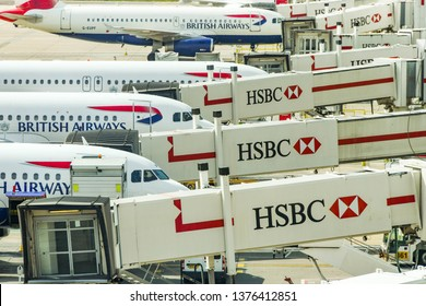 LONDON GATWICK AIRPORT, ENGLAND - APRIL 2019: British Airways planes linked up to passenger air bridges carrying HSBC signs at Gatwick Airport's South terminal building