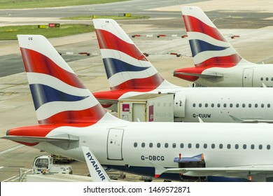 LONDON GATWICK AIRPORT, ENGLAND - APRIL 2019: Tail fins of three British Airways jets at Gatwick Airport