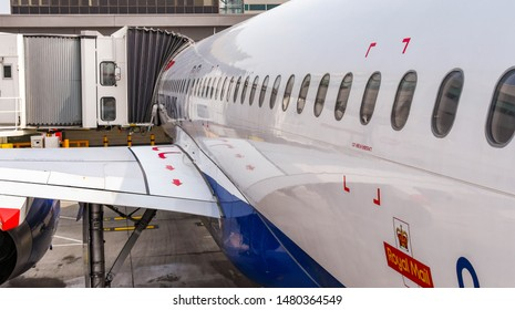 LONDON GATWICK AIRPORT, ENGLAND - APRIL 2019: Side of a British Airways Airbus jet attached to a passenger air bridge at  London Gatwick Airport