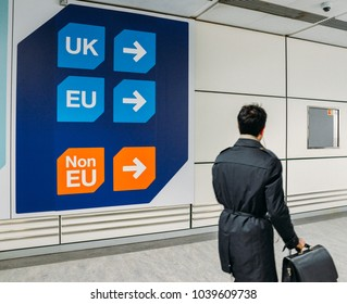 London Gatwick, March 2nd, 2018: Passenger walks past sign prior to immigration control pass a sign pointing towards queues for UK, EU and Non-EU passport holders