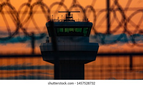 London Gatwick Sussex July 2019 UK The control tower at sunset through the razor wire that keeps the airport safe.
