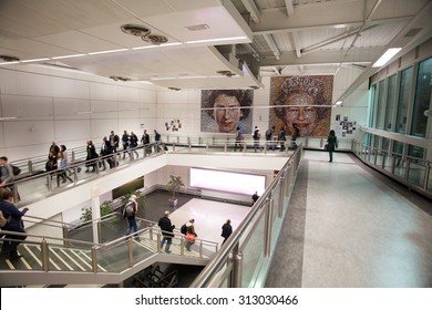 LONDON GATWICK, UK - CIRCA MARCH 2015: Passengers at Gatwick Airport walk by  'The People's Monarch': two big portraits of The Queen, made up of around 5,500 photos of British residents.