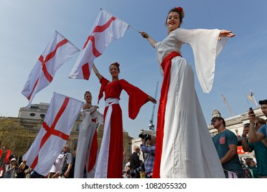 LONDON, GREAT BRITAIN, April 21, 2018 : Young women on stilts shake English flags for the Feast of St George in Trafalgar Square. Festivals are an integral part of English culture.
