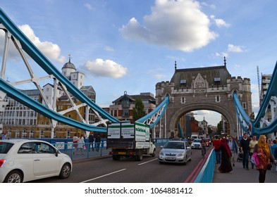 London, Great Britain - August 01, 2015: View to a typical scene with cars and pedestrians on the walkway of the Tower Bridge