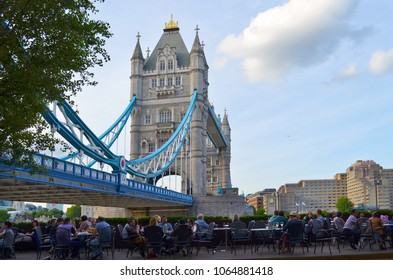 London, Great Britain - August 01, 2015: View of a typical evening scene with people in a restaurant below the Tower Bridge