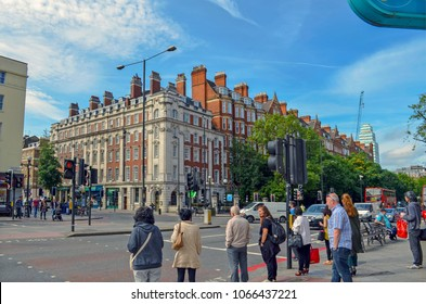 London, Great Britain - August 1, 2015: City life at the crossroad of Baker Street and Marylebone Street  with cars, a typical red bus, traffic lights and waiting people