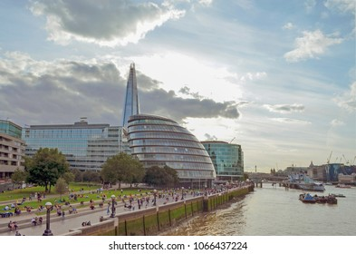 London, Great Britain - August 1, 2015: Promenade at the Thames with people, who relax at the end of the day in front of modern skyline of London