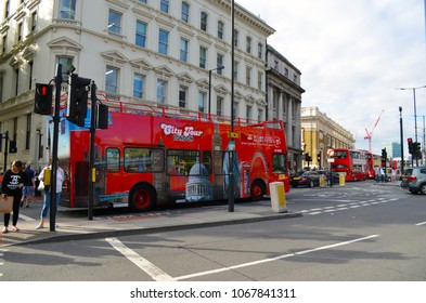 London, Great Britain - August 1, 2015: Looking to a typical red London bus and pedestrians on the walkway at a traffic light
