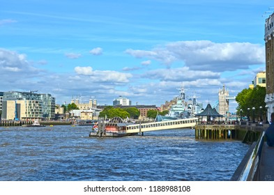 London, Great Britain - August 1, 2015: View over the River Thames to the cityscape of London in the direction of the Tower with a museum ship anchored there.