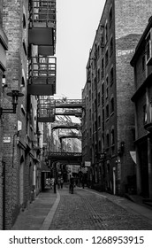 London, Great Britain - August 1, 2015: Black and white photo of a historic walkway through the Shad Thames with brick buildings in Bermondsey.