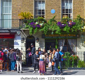 London, Great Britain - August 2, 2015: A group of tourists who want to be photographed with a bobby in front of baker street 221b.