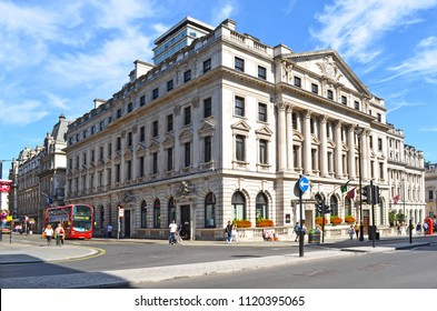London, Great Britain - August 2, 2015: Historic building at the crossroad of Waterloo Place and Charles II Street with a typical red bus, traffic lights and pedestrians