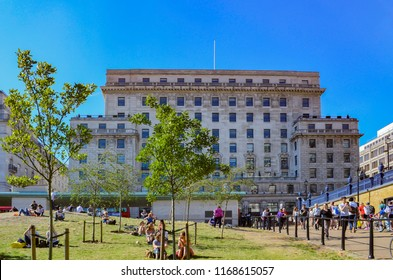 "London, Great Britain - August 2, 2015: People relaxing in London's ""Green Park"". In the background you can see the facade of an old building at Piccadilly."