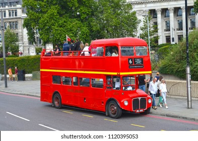 London, Great Britain - August 3, 2015: Looking to a typical red London bus for sightseeing with tourists and pedestrians on the walkway