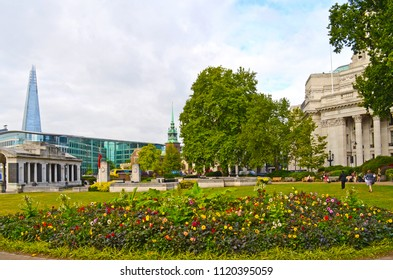 London, Great Britain - August 3, 2015: Trinity Square Gardens with view to Tower Hill Memorial and The Shard at the left, All Hallows-by-the-Tower church in the midle and Trinity House at right side