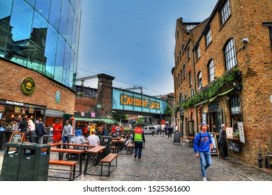 LONDON, GREAT BRITAIN, JUNE 3: HDR image of tourists walking along the colorful houses and shops in Camden Lock near the Camden Town on blue sky, London, UK, June 3, 2019