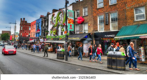 LONDON, GREAT BRITAIN, JUNE 3: HDR panoramic image of tourists walking along the colorful houses and shops in Camden Town on blue sky, London, UK, June 3, 2019