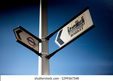 London, Great Britain - May 12, 2012: Portobelloe Market and London Underground street signs on a lamppost with a blue sky behind.