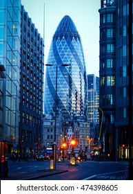 LONDON, GREAT BRITAIN - MAY 18, 2014. 30 St Mary Axe building in London, with surrounding buildings, city traffic and people, in the evening.