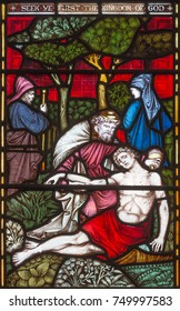 LONDON, GREAT BRITAIN - SEPTEMBER 19, 2017: The Parable of the Good Samaritan  on the stained glass in St Mary Abbot's church on Kensington High Street.