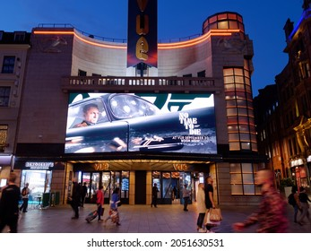 London, Greater London, England, September 21 2021: No Time To Die Bond Film advertised at the Vue Cinema in Leicester square at night as pedestrians pass by.