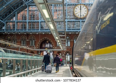 London, Greater London / UK - 30 March 2017: Passengers with luggage walking away from the Eurostar in Saint Pancras International station, with the metal arcade and clock above