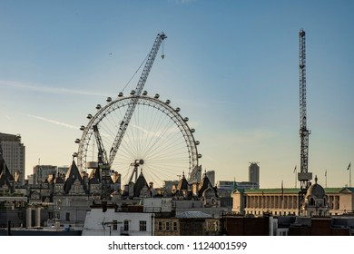London, Greater London / United Kingdom - May 10 2018: Sunrise over central London rooftops with the London Eye and some cranes in the background