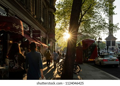 London, Greater London / United Kingdom - May 06 2018: Sunset over Trafalgar Square seen from a sidewalk with the sun in the center