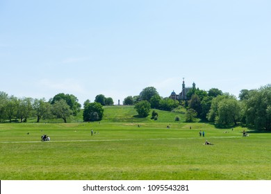 London, Greenwich, UK - May 15th, 2018: The meadow in front of Greenwich Observatory. People are relaxing on it, taking advanage of the blue sky.