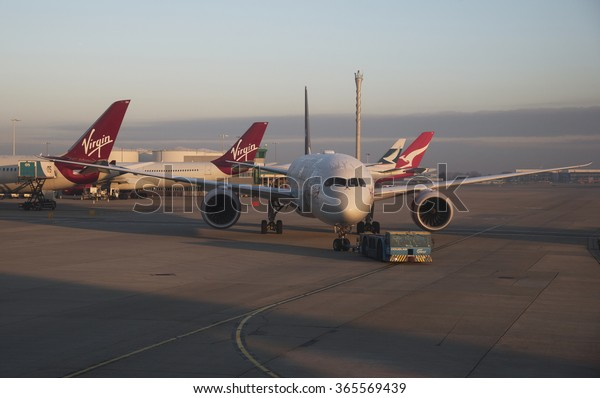 LONDON HEATHROW AIRPORT - 19 JANUARY 2016 - Early winter morning a Virgin Atlantic passenger jet being moved using an aircraft tractor at Heathrow London Airport