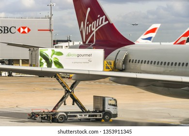 LONDON HEATHROW AIRPORT, ENGLAND - FEBRUARY 2019:  A Gate Gourmet scissor lift vehicle loading catering supplies through the rear door of a Virgin Atlantic airliner at London Heathrow Airport.