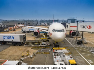 LONDON HEATHROW AIRPORT - JUNE 2018: Wide angle view of air freight being loaded into the cargo hold of a Virgin Atlantic Airbus A330 at London Heathrow Airport.