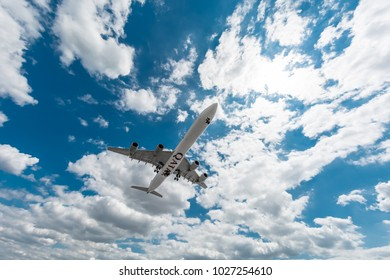 LONDON, HEATHROW / UK - 15 JULY 2014: the big aircraft Airbus 340 Qatar Airways delivers passengers and cargo, lands in the airport, wide view of overflying above with a cloudy sky