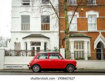 London- January, 2021: A classic old Mini Cooper parked on upmarket London street of terraced houses