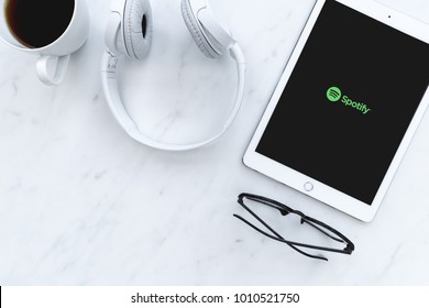 LONDON - JANUARY 25, 2018: Music headphones and Spotify music streaming app on white iPad tablet computer